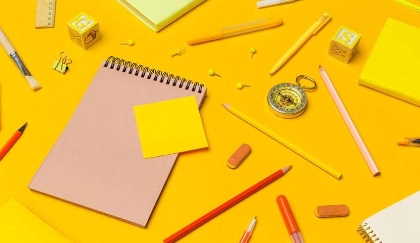 Schreibutensilien vor gelbem Hintergrund, bildlich für Texte für Rechtsanwälte