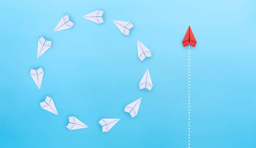 Weiße Papierflieger fliegen auf der Stelle im Kreis und ein roter Papierflieger mit geradem Kurs - Mindset für Kanzleimarketing