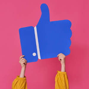 Facebook-Like aus Pappe wird von zwei Händen hoch gehalten vor pinken Hintergrund