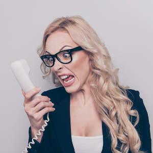 Eine Rechtsanwältin schaut den Telefonhörer genervt an und schreit rein - bildlich für: was beim Onlinemarketing für Rechtsanwälte alles schieflaufen kann